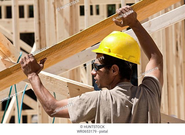 Carpenter lifting a laminated beam at a construction site