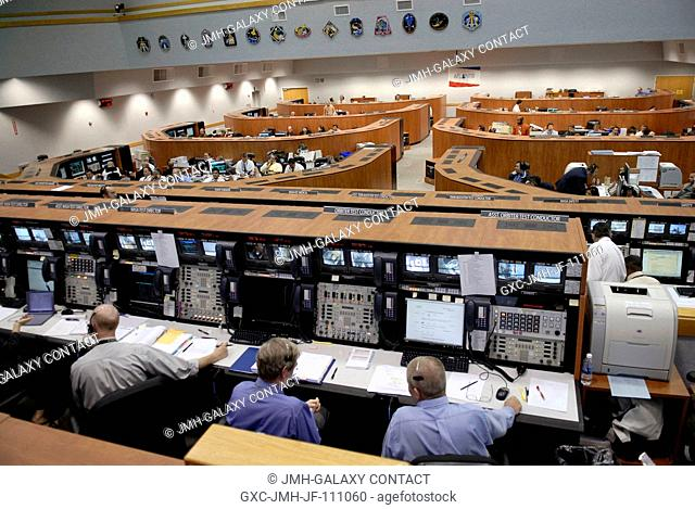 The space shuttle launch team monitors the progress of Space Shuttle Atlantis' countdown from consoles on the main floor of Firing Room 4 in Kennedy's Launch...
