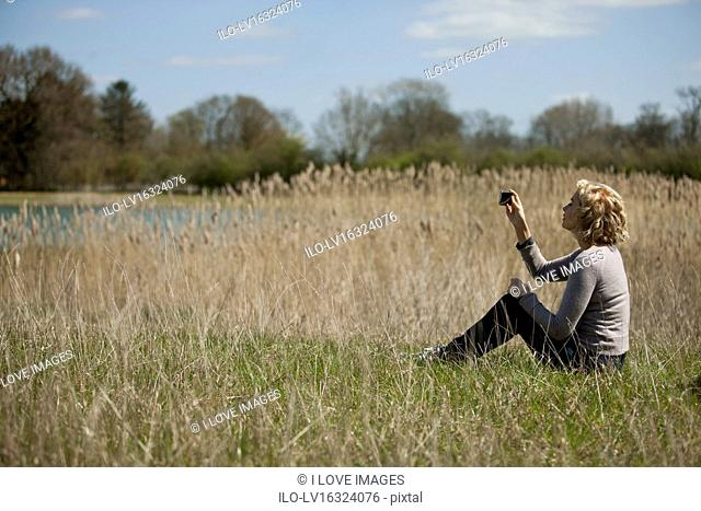 A mature woman sitting in long grass, taking a photo with a smartphone