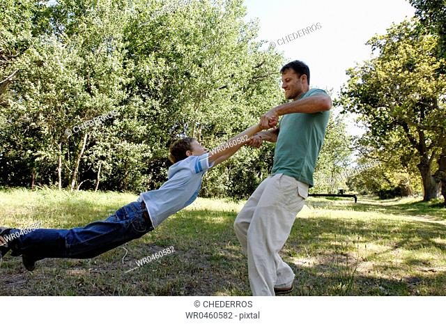 Side profile of a mid adult man swinging his son in a park
