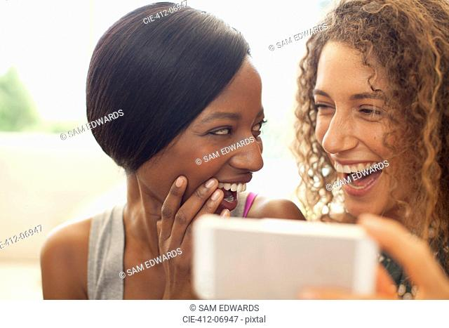 Women using cell phone on sofa