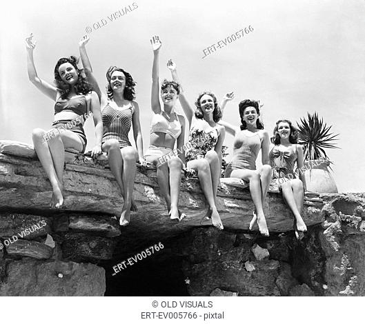 Low angle view of a group of women sitting on a stone structure and waving their hands All persons depicted are not longer living and no estate exists Supplier...