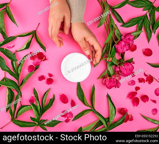 two hands of a young girl with smooth skin and a jar with thick cream and burgundy peonies with green leaves, top view, concept of anti-aging procedures for...