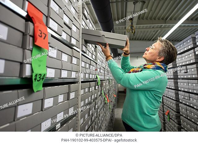11 December 2018, Hessen, Bad Arolsen: Nicole Dominicus, Head of Archive Administration, pulls a slipcase of the Central Index of Names (ZNK) from a file...