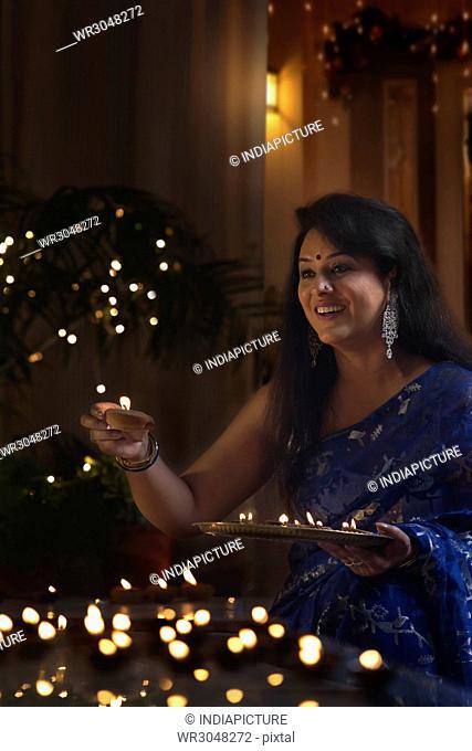 Smiling woman holding earthen lamp at diwali