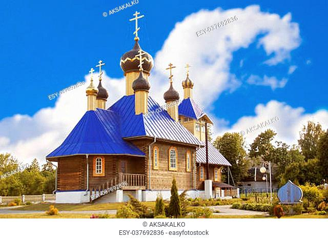 Wooden Orthodox church with golden domes and crosses