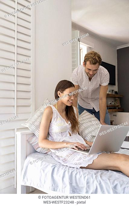 Smiling young couple with laptop in bedroom
