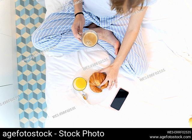 Young woman sitting on bed and having a coffee