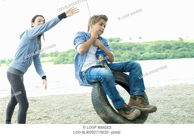 A girl and a boy playing on a tyre hanging from a tree on the shore beside Bala Lake in Wales