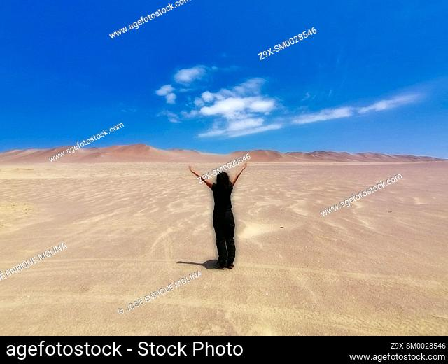National Reserve of Paracas, woman in the desert, Ica department, Perú. South America