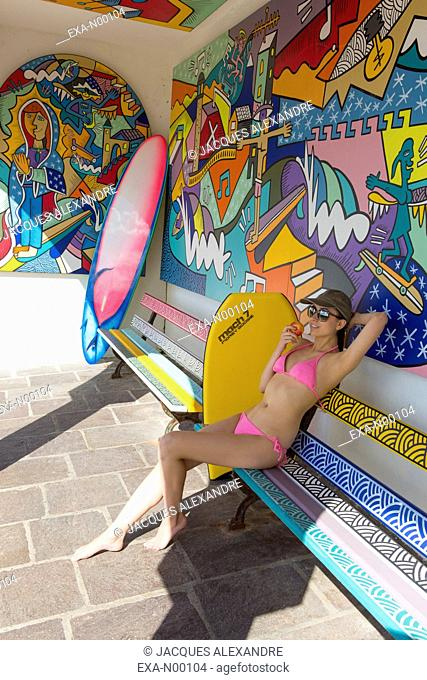Surfer girl making a rast surrounded by graffitis