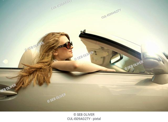 Teenage girl showing off in sports convertible