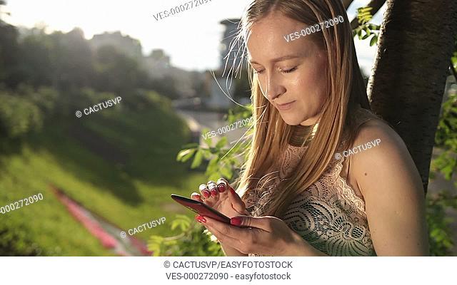 Joyful woman texting on smartphone in park