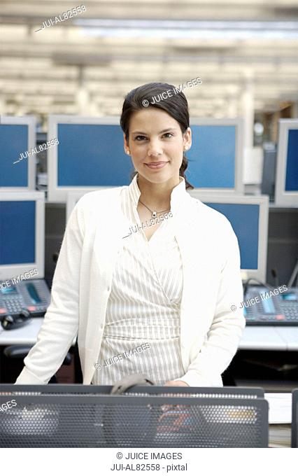 Businesswoman smiling and standing at desk