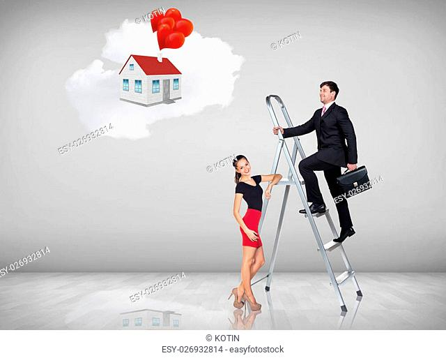 Businessman with woman assistant climbing a ladder with motivation background
