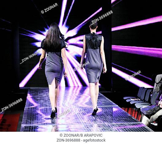 beautiful young fashion model woman walking on fashion show event