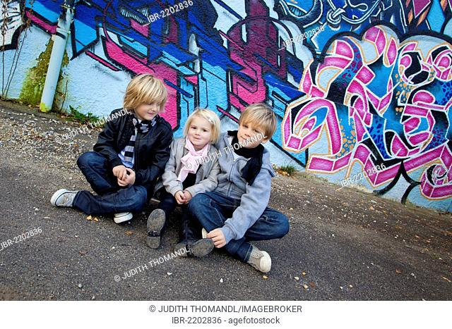 Siblings, 2, 5 and 7 years old, sitting on a skateboard in front of a wall with graffiti