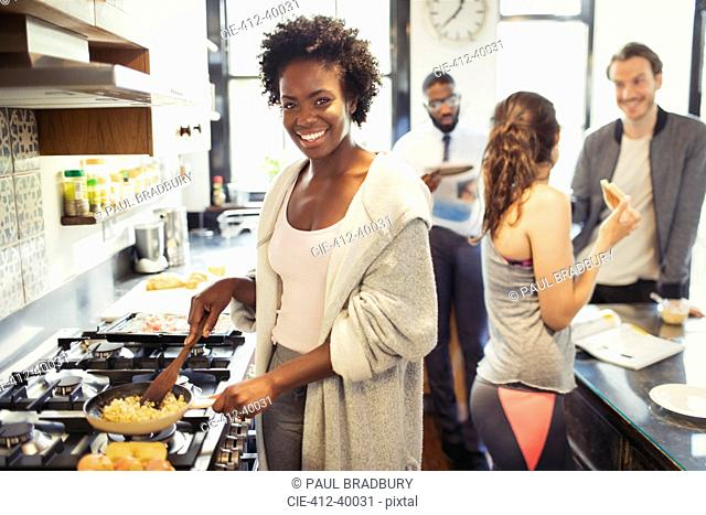 Portrait smiling woman cooking scrambled eggs at stove in kitchen