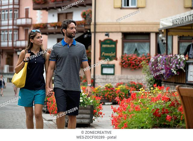 Smiling couple strolling in a town