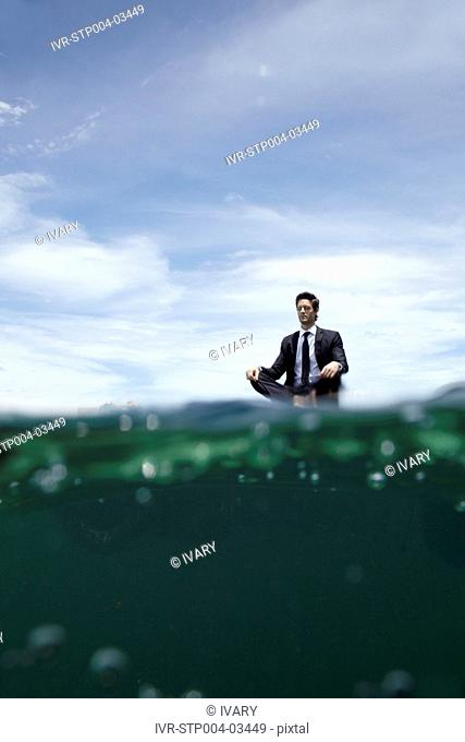 A businessman meditating on a dock