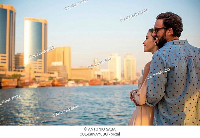 Romantic couple looking out at Dubai marina, United Arab Emirates