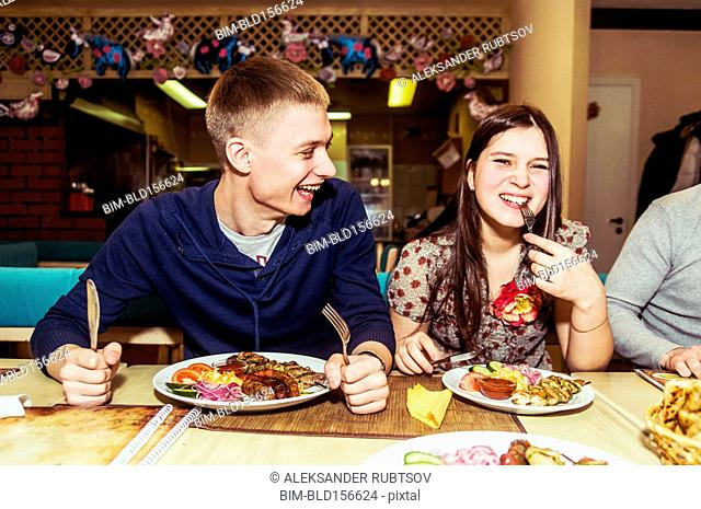 Caucasian couple laughing in restaurant