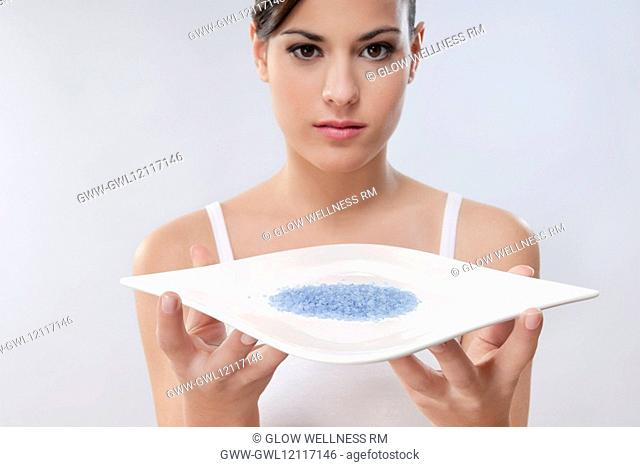 Portrait of a woman holding a tray of bath crystals