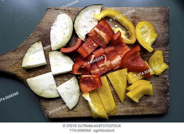 Sliced Aubergine and Bell Peppers on Chopping Board