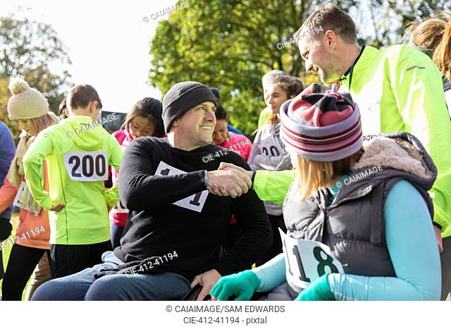 Runner shaking hands with man in wheelchair at charity race in sunny park