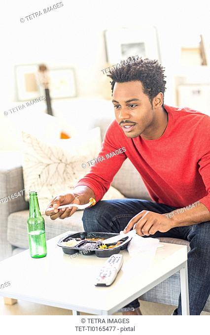 Man eating dinner and watching television