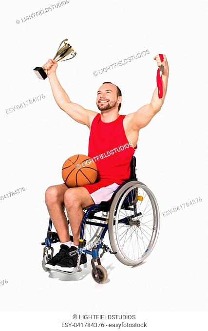 Disabled basketball player in wheelchair with champion goblet and gold medals isolated on white