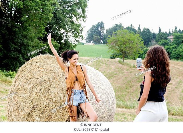 Friends taking photo by hay bale on field, Città della Pieve, Umbria, Italy
