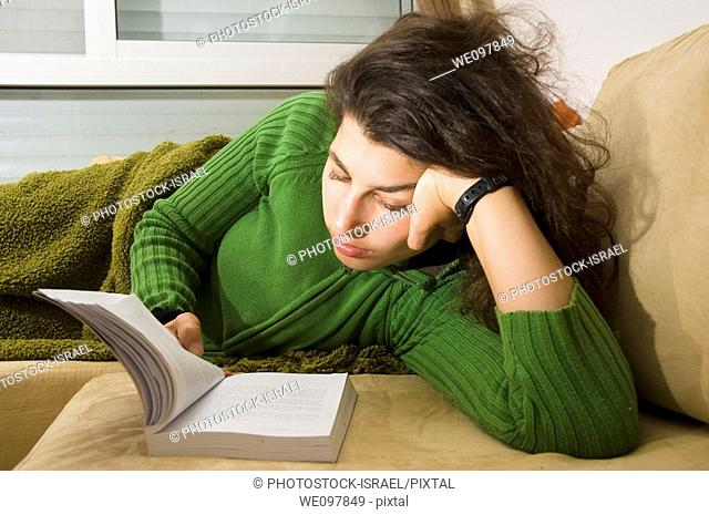 Young woman in her 20s reading a book while lying on a bed model release available Selective lighting