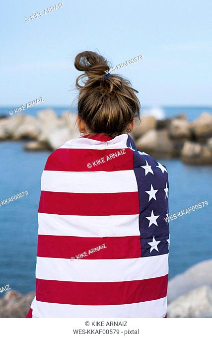 Back view of young woman standing in front of the sea wrapped in US American flag