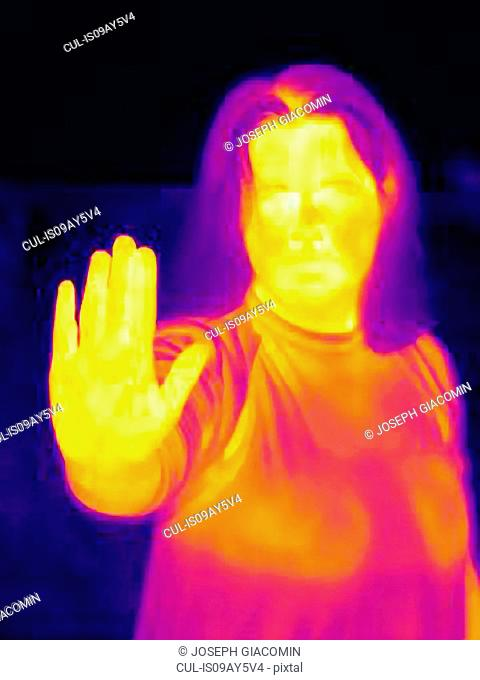 Thermal image of woman raising hand in stop gesture
