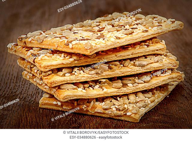 Stack of cereal cookies with seeds on a wooden table