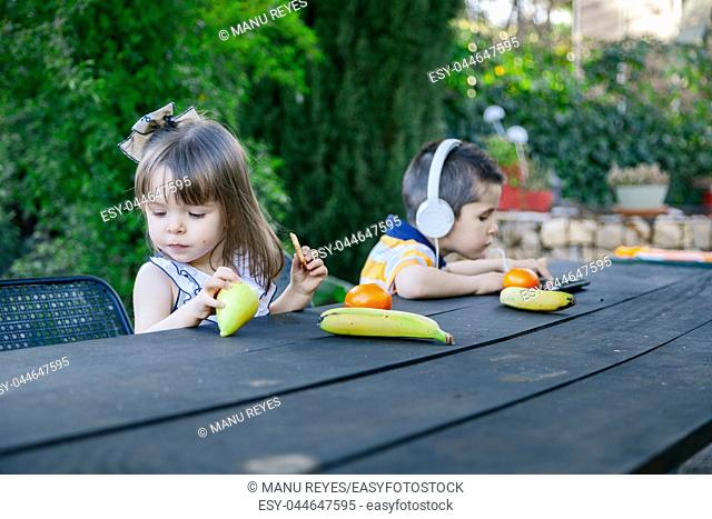 Children playing outdoors with different fruits. Madrid, Spain