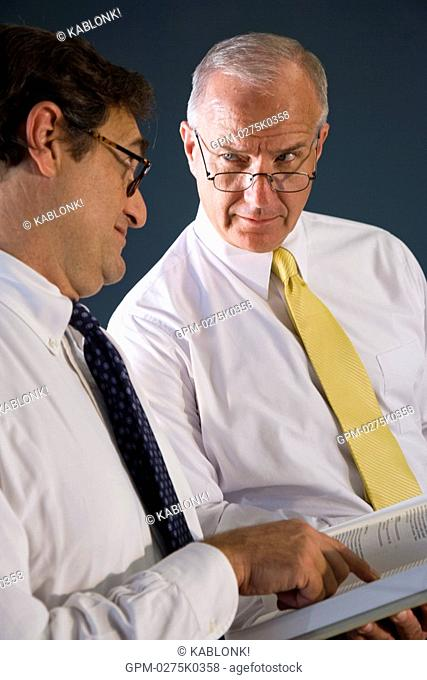 Businessmen standing in conference room researching information in books
