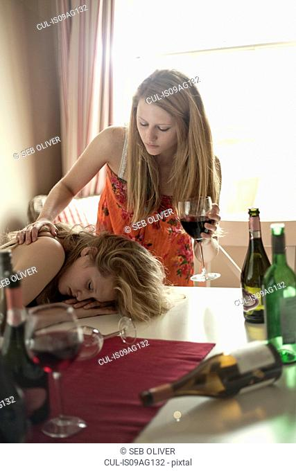 Drunk teenage girls at table with wine bottles and glasses