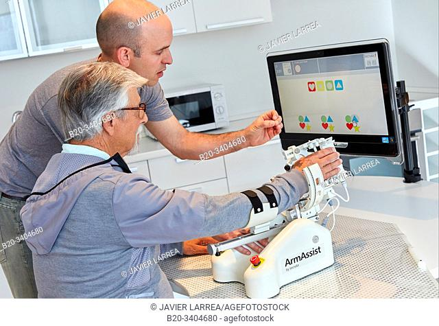 Patient with assistive robot for upper limb rehabilitation, The robot ArmAssist allows passive, assisted and active training of the arm and hand