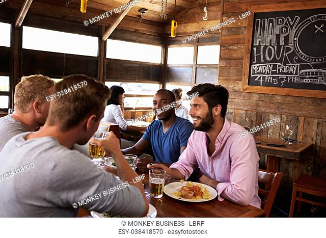 Four male friends at lunch together in restaurant, close up