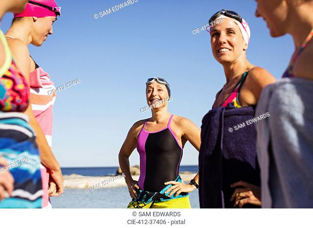 Smiling female open water swimmers wrapped din towels on sunny beach
