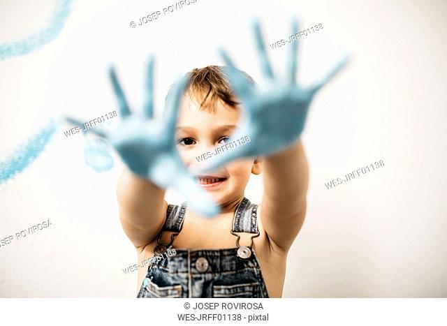 Portrait of smiling little boy showing his palms full of light blue colour