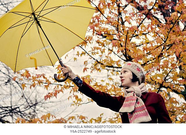 Woman holding yellow umbrella, autumn