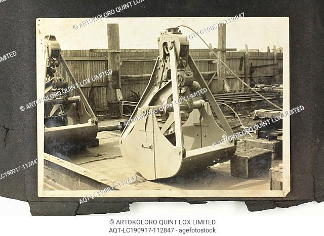 Photograph - A.T. Harman & Sons, Closed Excavator Bucket in a Yard, circa 1923, One of three black and white photographs attached to an album page