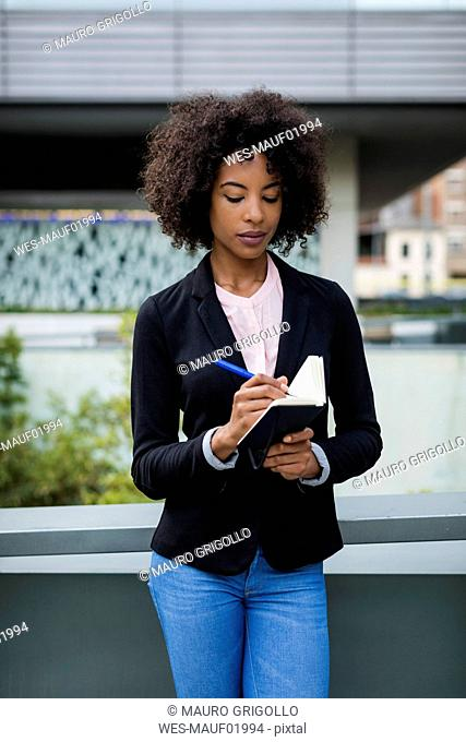 Portrait of businesswoman taking notes outdoors