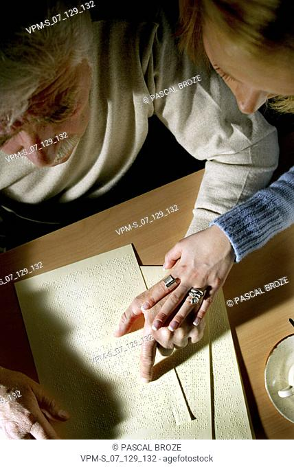 High angle view of a young woman teaching her father a book in Braille