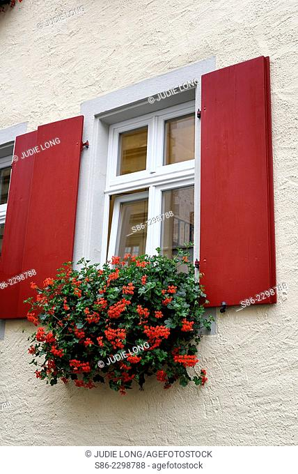 Traditional Red Shuttered German Window, With Geranium Pots at the Base. The Geraniums are supposed to keep out insects