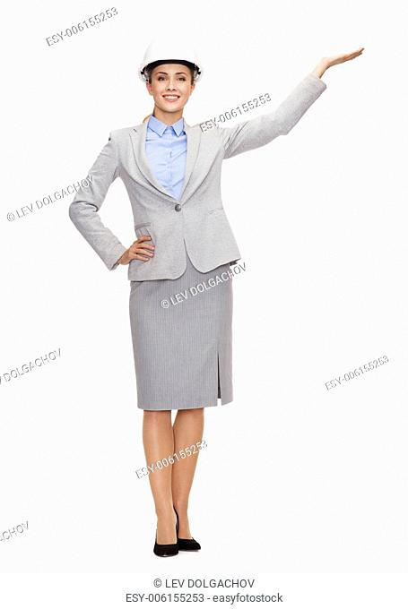 building, developing, advertising and architecture concept - friendly young smiling businesswoman in white helmet holding something on palm