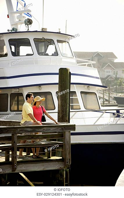 Mid-adult Caucasian couple at dock with boat in background